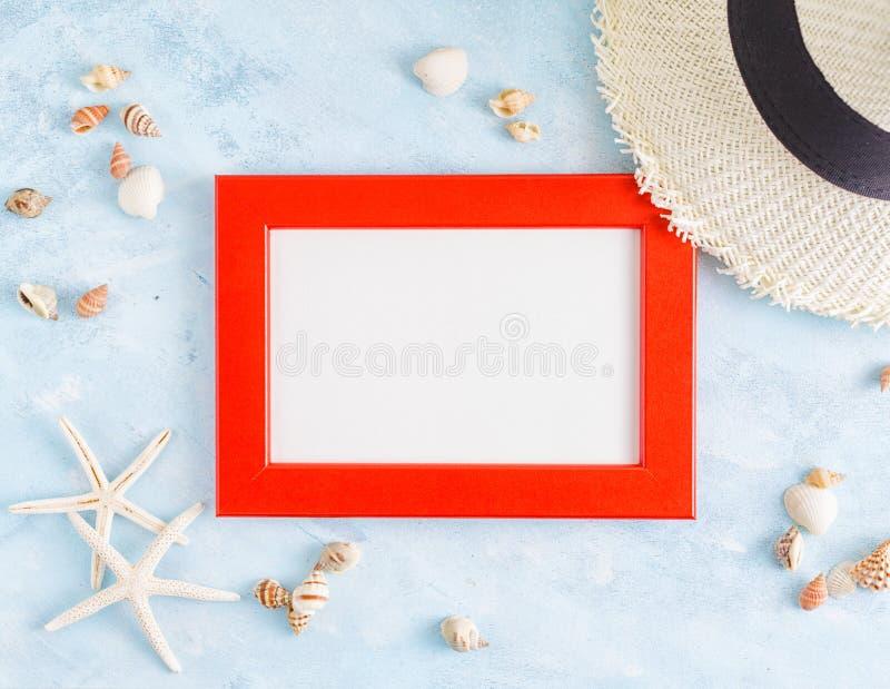Maqueta puesta plana del verano de la visión superior: marco, conchas marinas, sombrero de paja y estrellas de mar rojos, de la f imagen de archivo libre de regalías