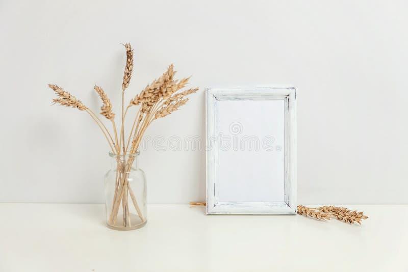 Maqueta vertical del marco con el ramo del centeno salvaje en el florero de cristal cerca de la pared blanca imagenes de archivo