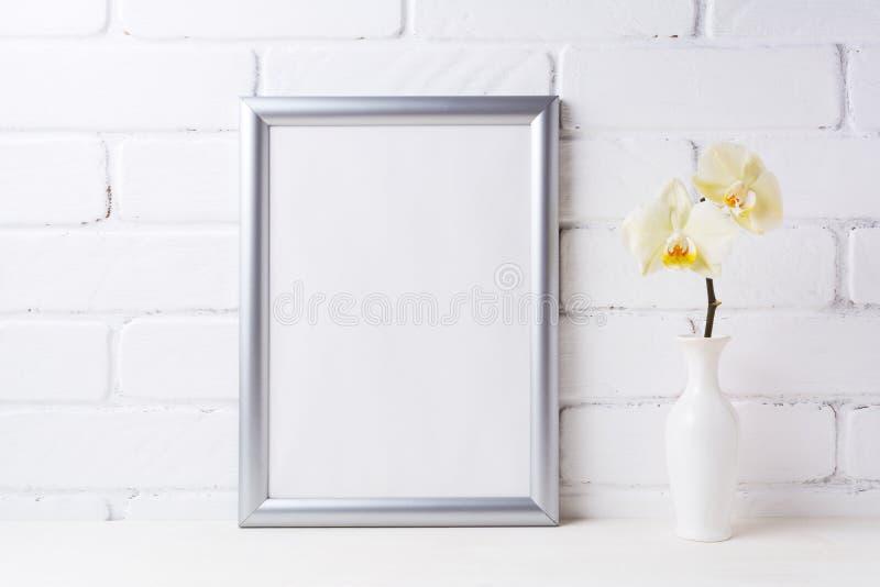 Maquette argentée de cadre avec l'orchidée jaune molle dans le vase photos stock