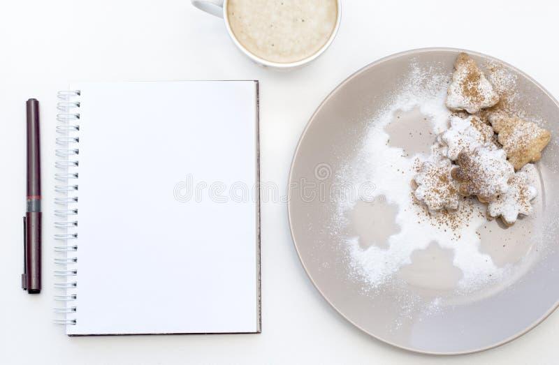 Maquette avec le bloc-notes vide, la tasse de café et le biscuit Biscuits et cappuccino de nouvelle année De Noël de matin toujou photographie stock libre de droits