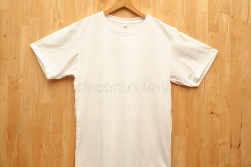 Maquette blanche blanche vide de MOIS-chemises de T-shirts de TBlank accrochant sur la vue en bois de mur, d'avant et de dos Pr?p photo libre de droits