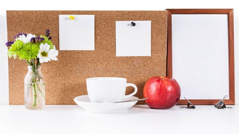 Maquette Cadre vide, corkboard avec deux autocollants blancs propres goupillés à lui Tasse blanche, pomme rouge et un petit bouqu photographie stock