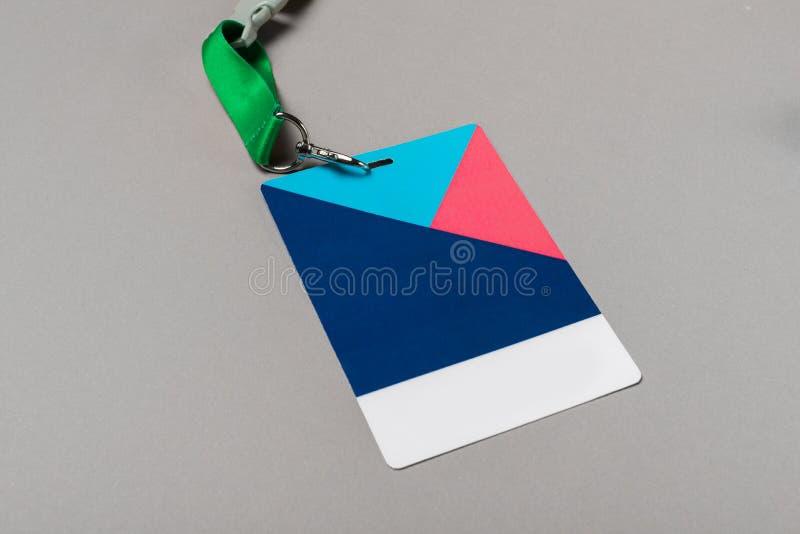 Maquette d'insigne de couleur sur le fond gris Moquerie vide simple d'étiquette de nom avec de la ficelle de couleur image libre de droits