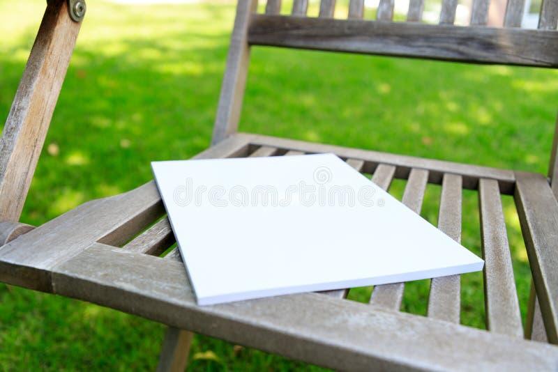 Maquette d'une couverture de magazine sur une chaise en bois dans le jardin au su photographie stock libre de droits