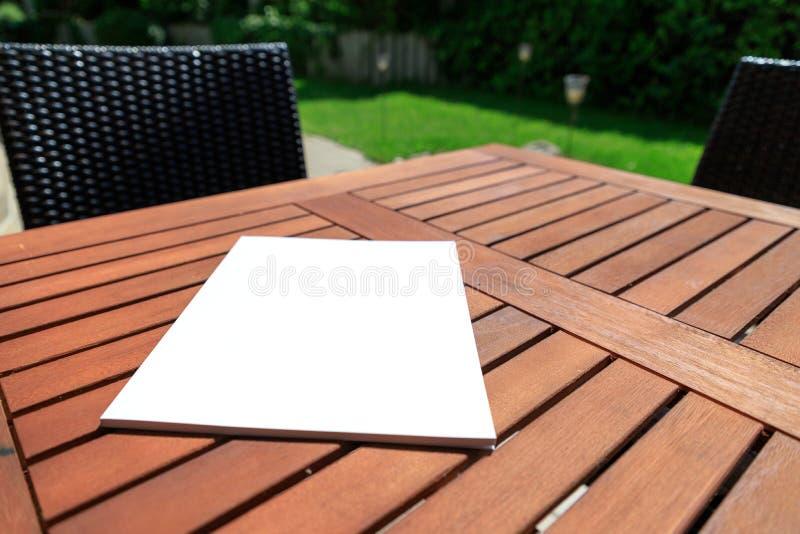Maquette d'une couverture de magazine sur une table en bois dans le jardin au su images stock