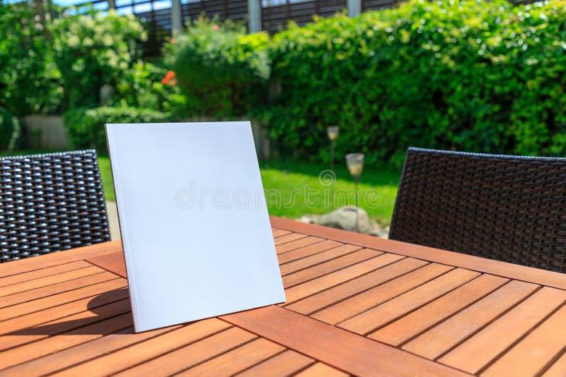 Maquette d'une couverture de magazine sur une table en bois dans le jardin au su photographie stock