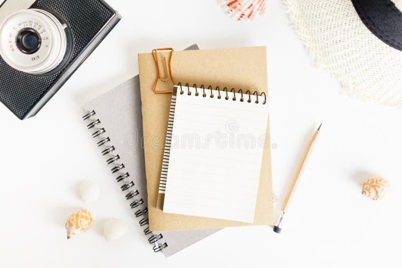 Maquette de bloc-notes étendue par appartement de vue supérieure : crayons, caméra de photo, chapeau, coquillages sur le fond bla photos libres de droits
