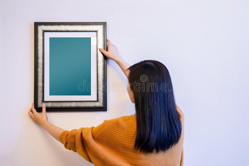 Maquette de cadre de photo avec le chemin de coupure Femme décorant un nouveau Ho photographie stock