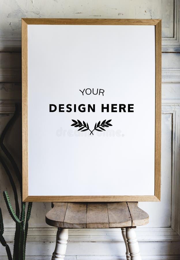 Maquette de cadre de photo sur une chaise par le mur images libres de droits