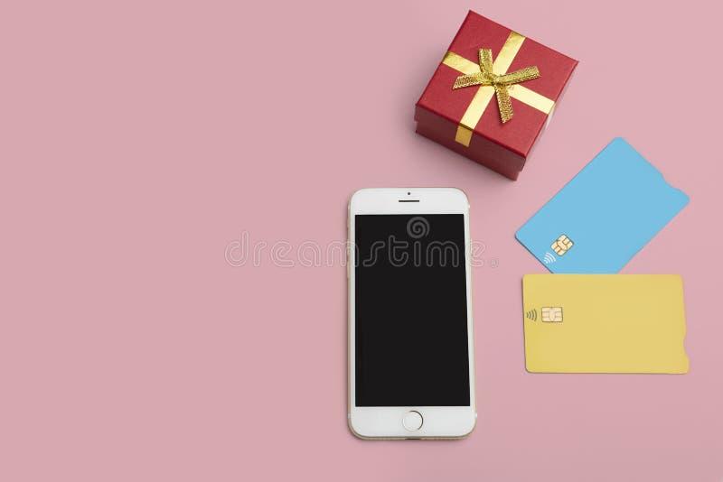 Maquette de deux cartes de crédit vierges de couleur, smartphone, boîte-cadeau sur le bureau rose vide Fond de maquette d'affaire images stock