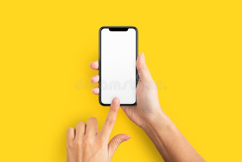 Maquette de main femelle tenant le téléphone portable avec l'écran vide images stock