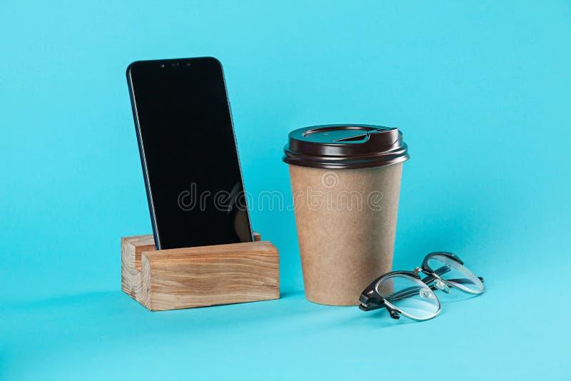 Maquette de papier à emporter de tasse de café d'isolement sur le fond bleu photo stock