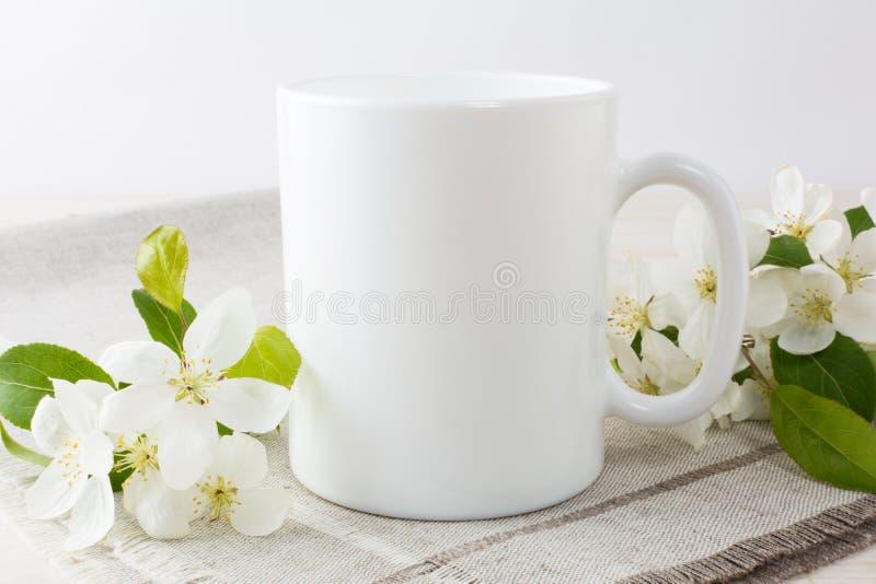 Maquette de tasse de café blanc avec la fleur de pomme photographie stock