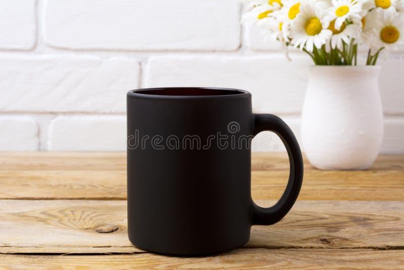 Maquette de tasse de café noir avec le bouquet de camomille dans le vase rustique images stock
