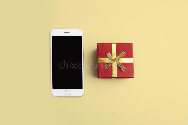 Maquette du smartphone boîte cadeau sur le bureau propre jaune vide