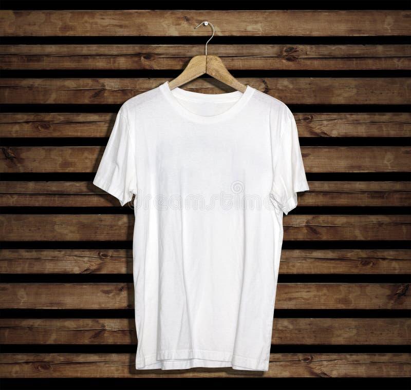 Maquette et calibre de T-shirt sur le fond en bois pour la mode et le concepteur photographie stock
