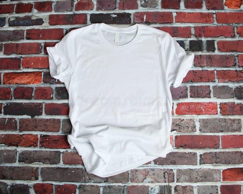 Maquette plate de configuration du tee-shirt blanc sur le fond de brique photographie stock