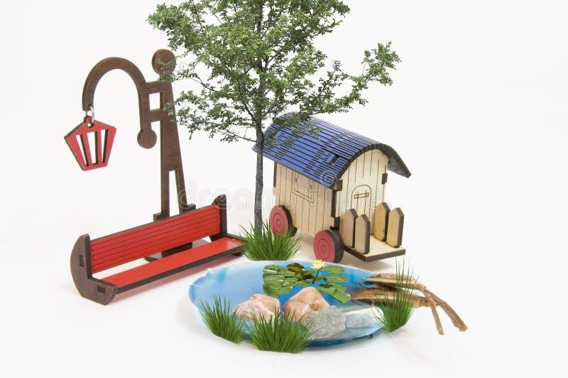 Maquette vermelho de madeira do banco de parque e ampola, lago pequeno, caravana, banana-da-terra fotografia de stock