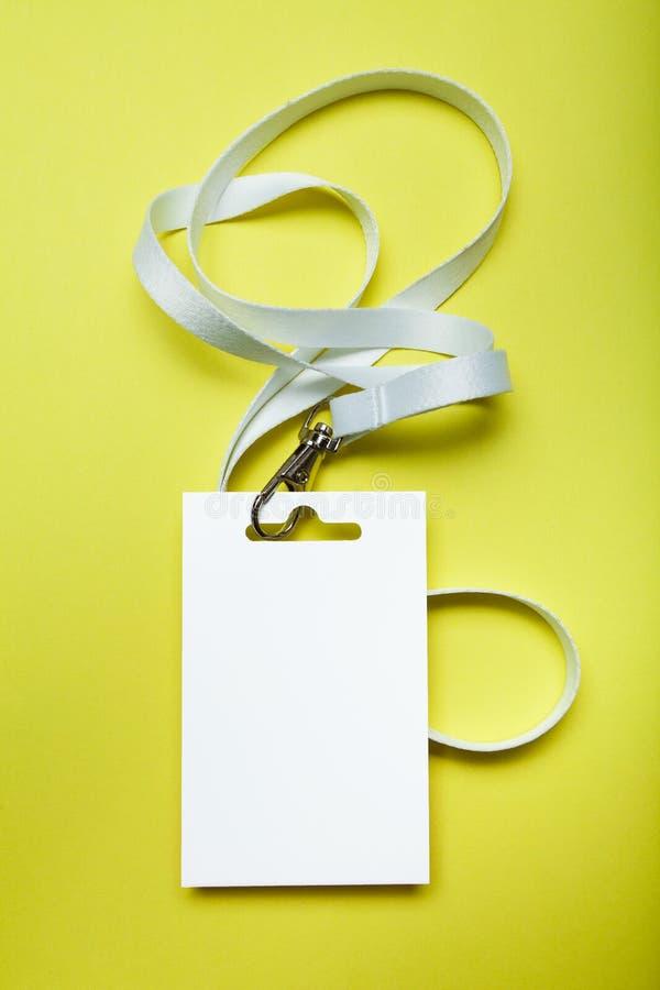 Maquette vide d'insigne d'isolement sur le fond jaune Étiquette de nom avec le ruban blanc, l'espace pour le texte vertical images stock