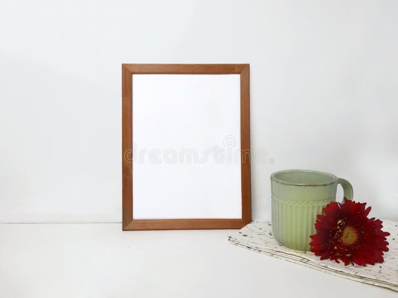 Maquette vide de cadre, tasse en céramique avec la fleur rouge sur le blanc photos libres de droits