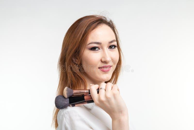 Maquilhador, beleza e conceito dos povos - jovem mulher coreana bonita que guarda escovas da composição no fundo branco fotos de stock royalty free