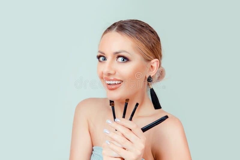 Maquilhador entusiasmado super da beleza que guarda escovas da sombra imagem de stock