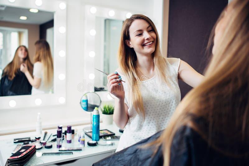 Maquilhador novo alegre que trabalha com um cliente que guarda uma escova fina que está no estúdio da composição fotos de stock
