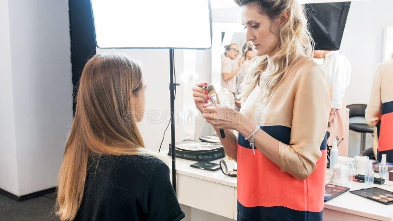 Maquilhador profissional que está no modelo novo no salão de beleza imagem de stock royalty free