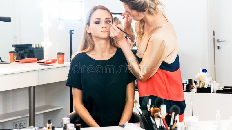 Maquilhador profissional que trabalha com modelo no estúdio fotos de stock royalty free