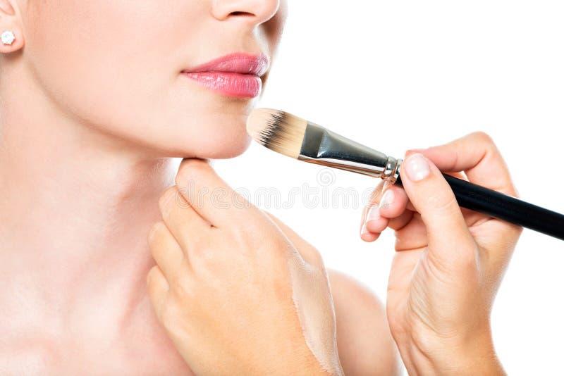 Maquilhador que aplica a fundação tonal líquida na cara foto de stock royalty free