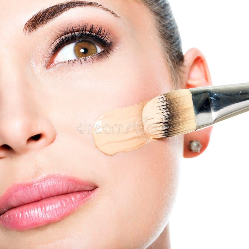 Maquilhador que aplica a fundação tonal líquida na cara imagens de stock