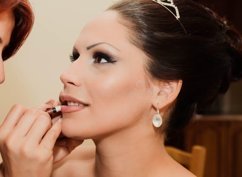 Maquilhador que aplica o batom a uma noiva Fim acima foto de stock