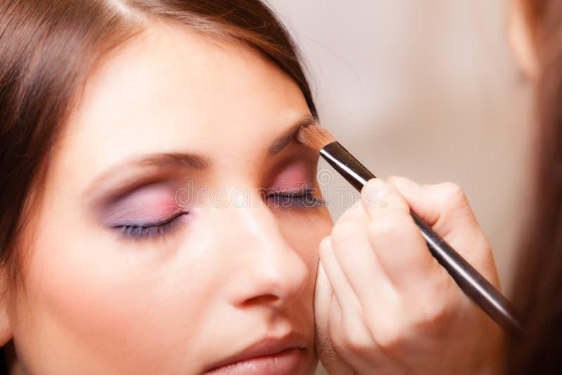 Maquilhador que aplica-se com o cosmético da escova na sobrancelha da mulher fotos de stock royalty free