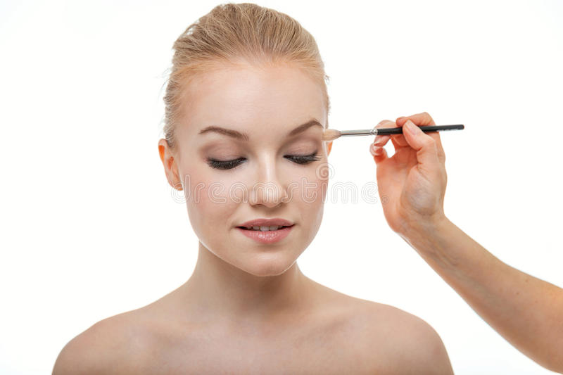 Maquilhador que aplica a sombra para os olhos para a jovem mulher bonita no fundo branco imagens de stock royalty free