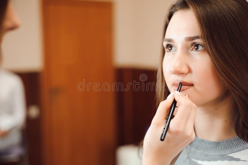 Maquilhador que cria a composição bonita para o modelo moreno foto de stock