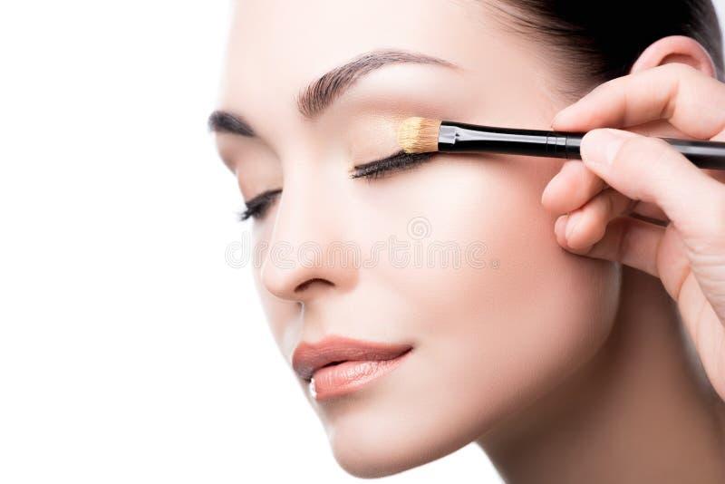 Maquilhador que usa a escova para aplicar a sombra para os olhos na cara da mulher foto de stock royalty free