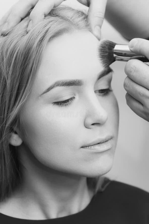 Maquillage d'école femme de pose à la mode Fille obtenant le maquillage sur le visage avec la brosse de poudre photographie stock