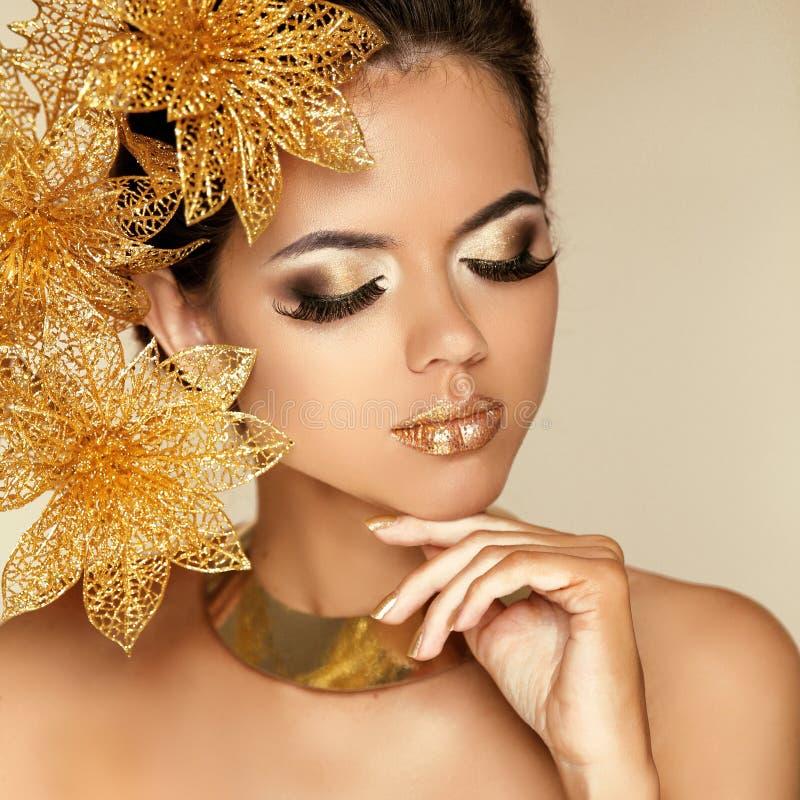 Maquillage d'oeil. Belle fille avec les fleurs d'or. Beauté Wom modèle photo stock