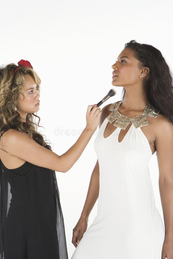 Maquillage de application femelle sur le visage du modèle photographie stock libre de droits