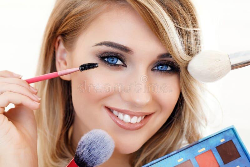 Maquillage de femme appliquant le plan rapproché eyeliner photographie stock libre de droits