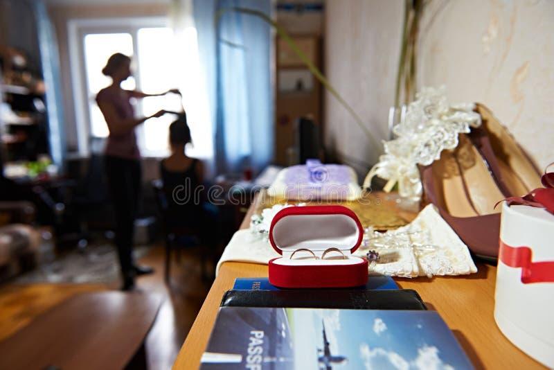 Maquillage de matin des anneaux de jeune mariée et de mariage sur la table photographie stock