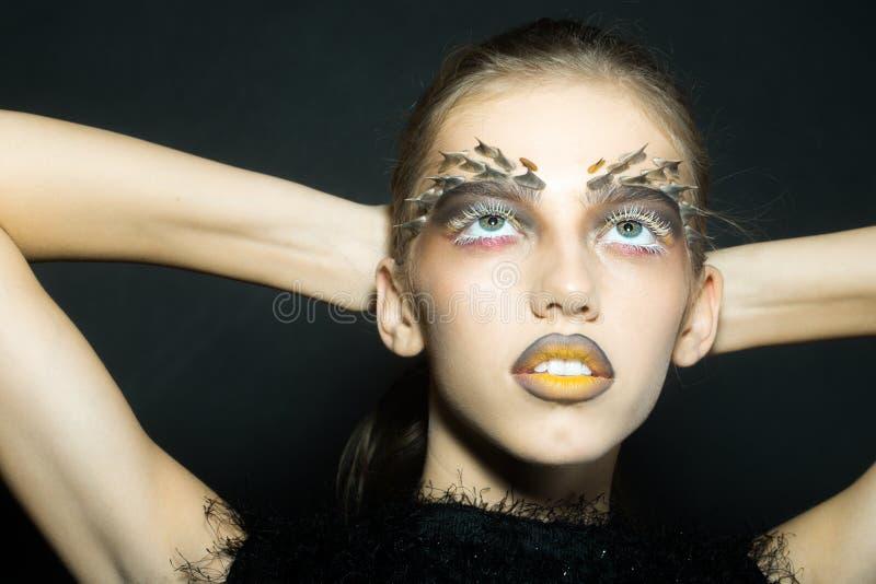 Portrait de plan rapproché d\u0027une belle jeune femme sauvage avec le maquillage  animal d\u0027or lumineux de singe avec des épines sur le visage dans le studio  sur