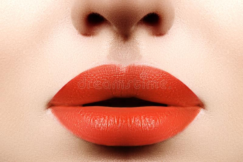 Maquillage lumineux de mode Macro de visage du ` s de femme Maquillage de lèvre de charme avec le rouge à lèvres orange Chirurgie photo libre de droits