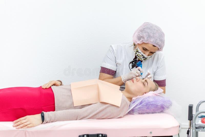 Maquillage permanent, tatouer des sourcils L'application de Cosmetologist composent image libre de droits