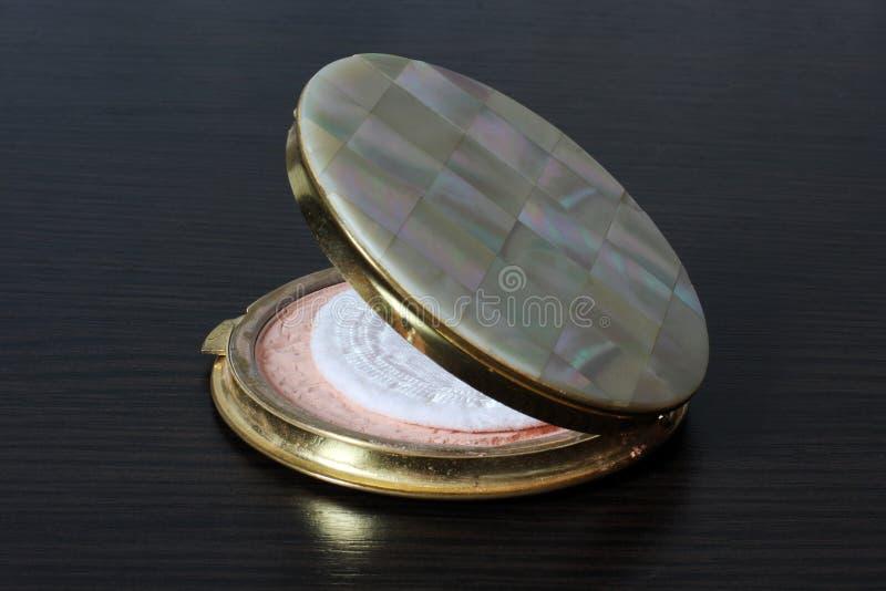 Maquillage Poudre de visage sur un fond noir toilette en cuir femelle de sujet de poudre de personne de soin annexe de cadre photographie stock libre de droits