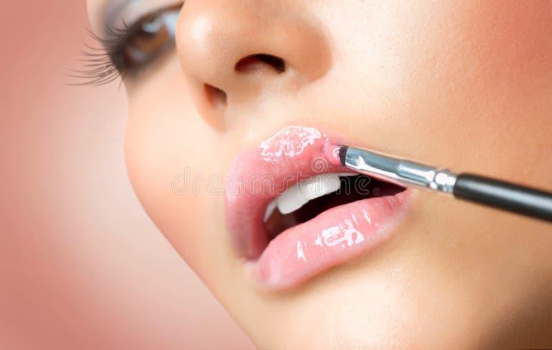 Maquillaje. Aplicación de Lipgloss fotografía de archivo libre de regalías