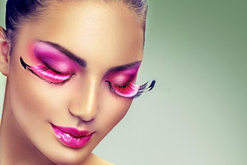 Maquillaje creativo del día de fiesta con las pestañas púrpuras largas falsas fotografía de archivo libre de regalías