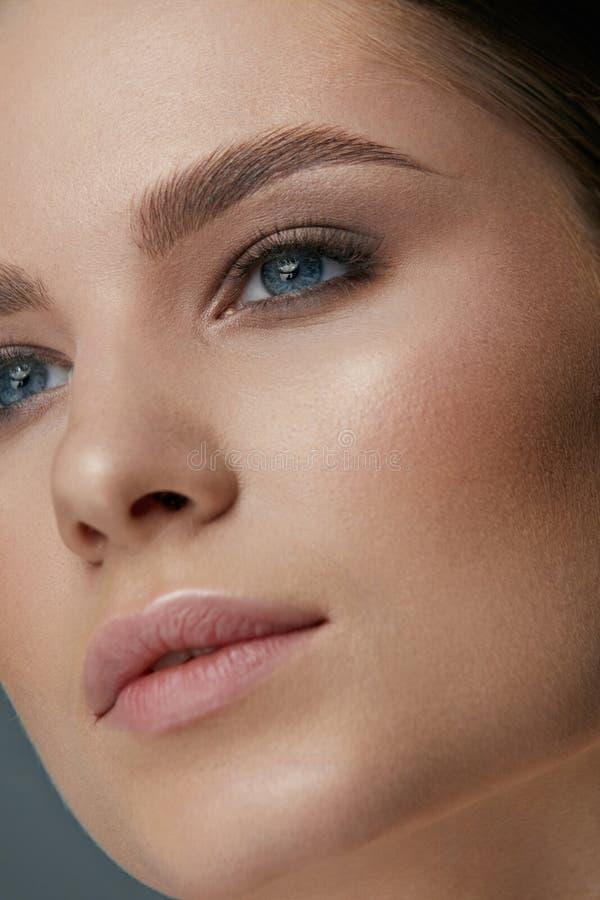 Maquillaje de la belleza Cara de la mujer con maquillaje de los ojos y de las cejas imagenes de archivo