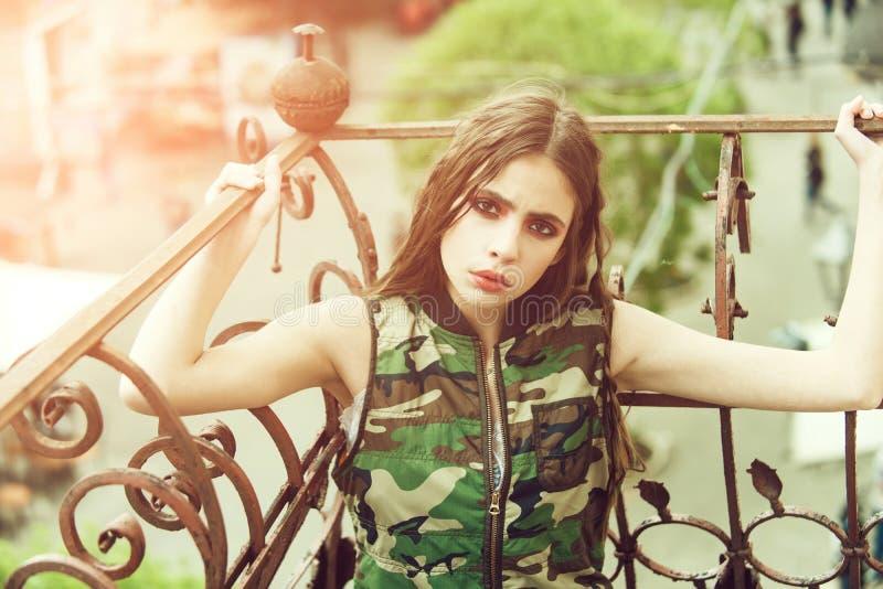 Maquillaje de la manera Muchacha bonita en el chaleco del camuflaje que sostiene los carriles metálicos del balcón foto de archivo libre de regalías