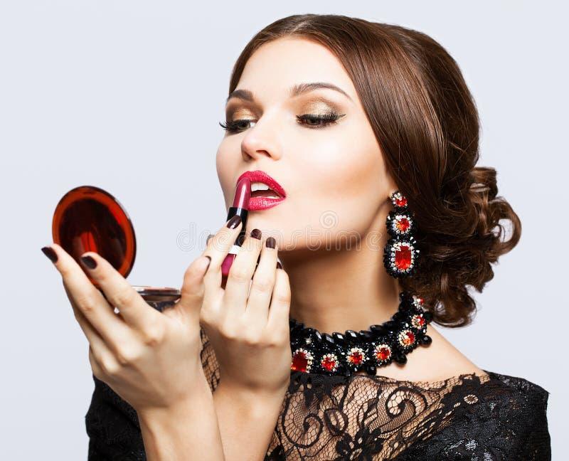 Maquillaje de la mujer morena hermosa joven en vestido negro con el labio foto de archivo